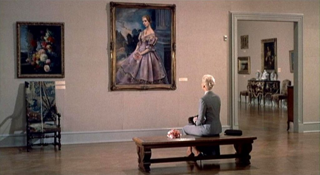 woman sitting on bench watching painting of woman in art gallery