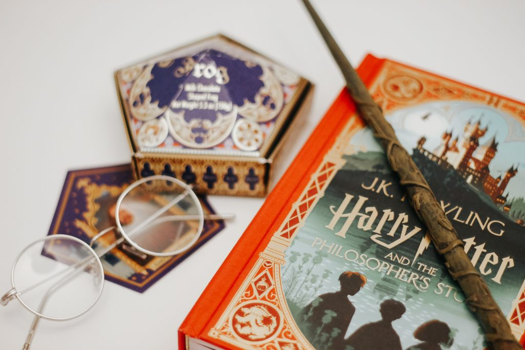 glasses book chocolate frog box and wand on white